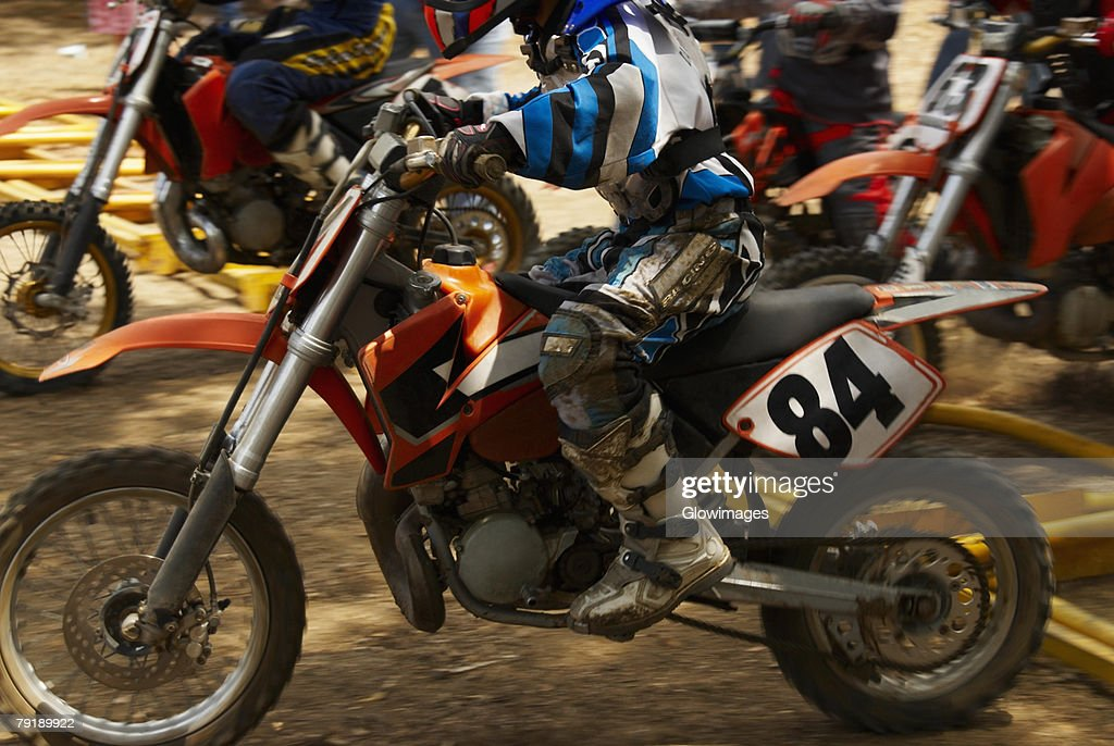 Side profile of motocross riders riding motorcycles : Foto de stock