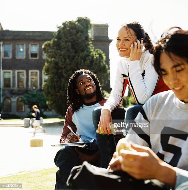 side profile of students sitting outdoors - incidental people stock pictures, royalty-free photos & images