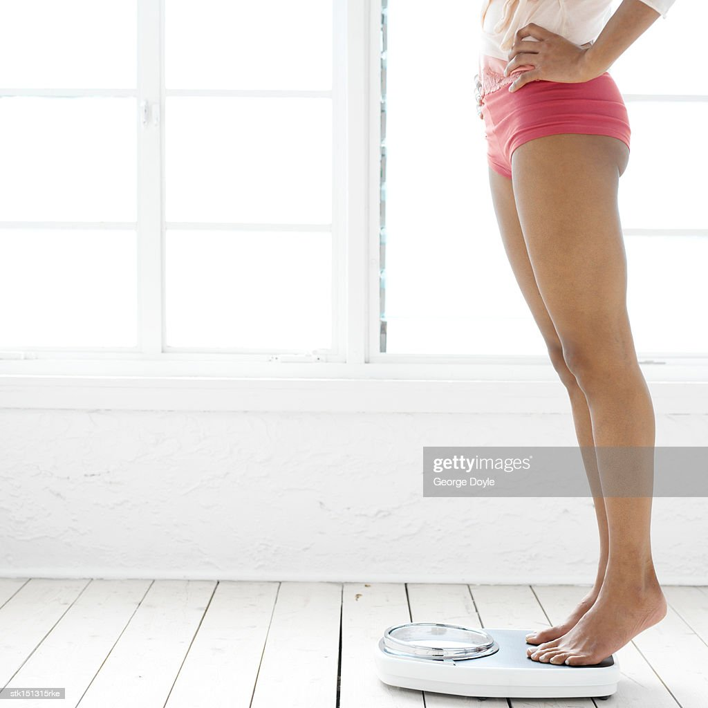 Side profile of the legs of a woman standing on a weighing scale : Stock Photo