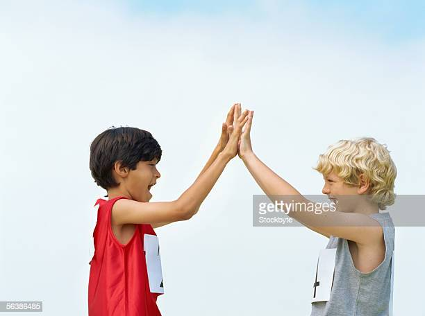side profile of two boys giving high-five