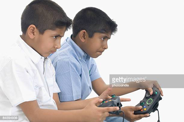 Side profile of two boys playing video game
