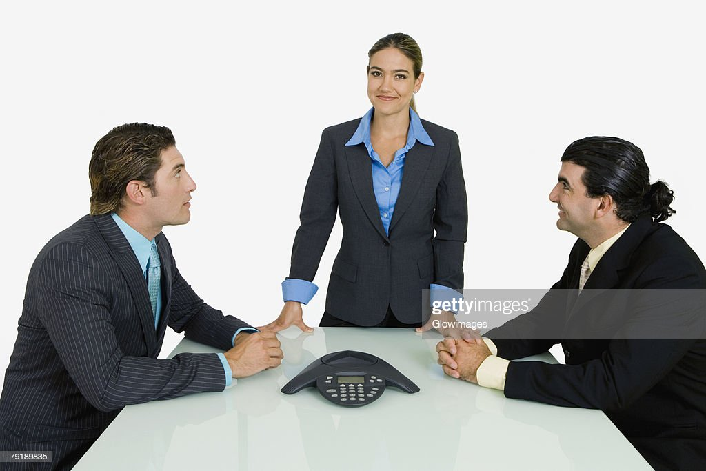 Side profile of two businessmen and a businesswoman in a conference room : Stock Photo