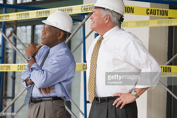 side profile of two engineers standing in a construction site - the black tape project stock-fotos und bilder