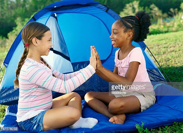 side profile of two girls playing outside a tent - only girls stock pictures, royalty-free photos & images