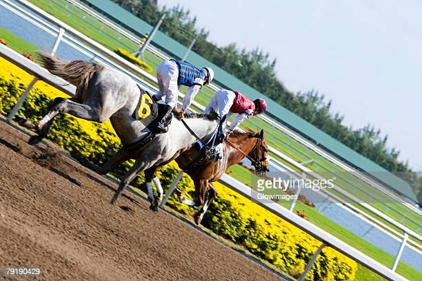 Side profile of two jockeys riding horses in a horse race