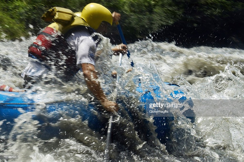 Side profile of two people rafting in a river : Foto de stock