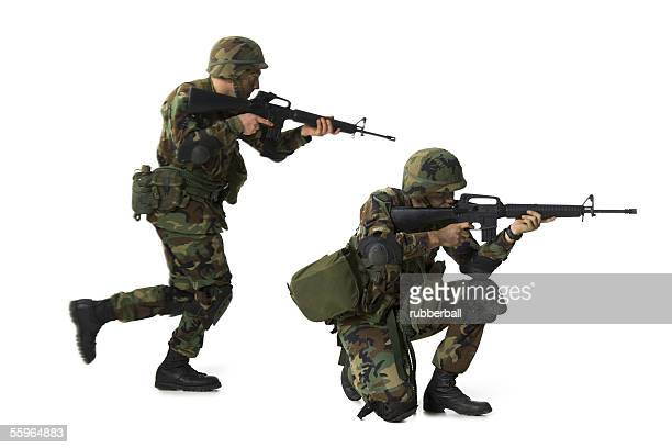 side profile of two soldiers aiming their rifles - boots rifle helmet stock pictures, royalty-free photos & images