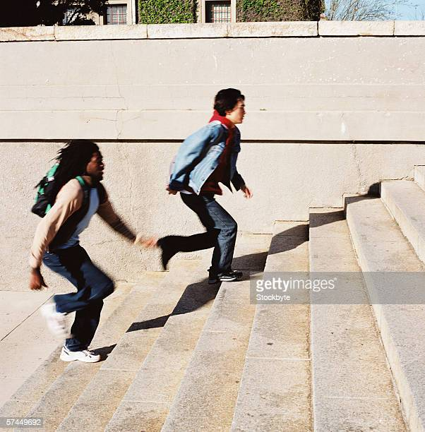 side profile of two students carrying backpacks running up a flight of stairs