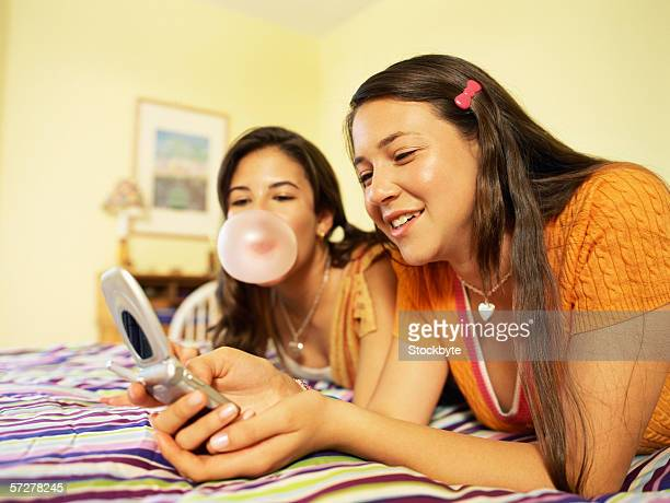 Side profile of two teenage girls lying on bed and holding a mobile phone