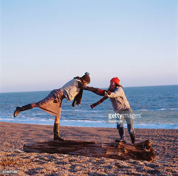 side profile of two young women balancing on driftwood lying on the beach