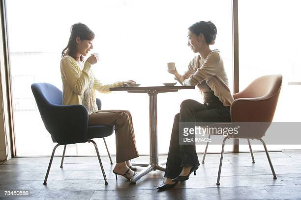 Side profile of two young women sitting in a restaurant