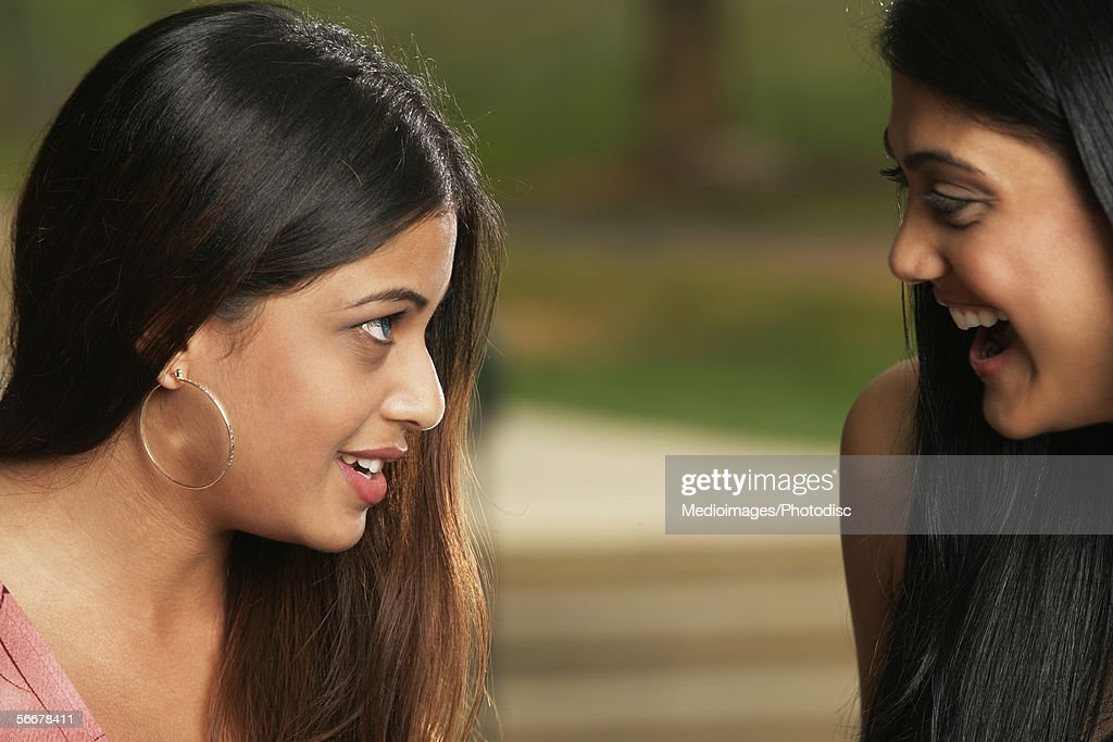 Side profile of two young women smiling at each other : Stock Photo