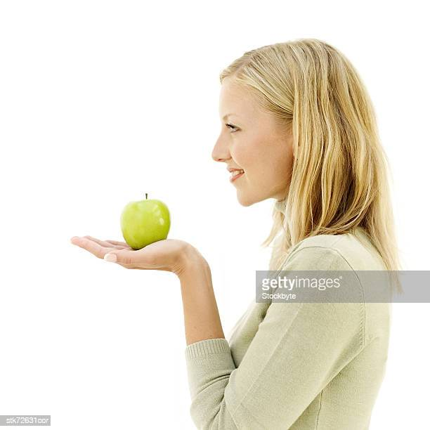 side profile of woman holding a fresh green apple in her palm