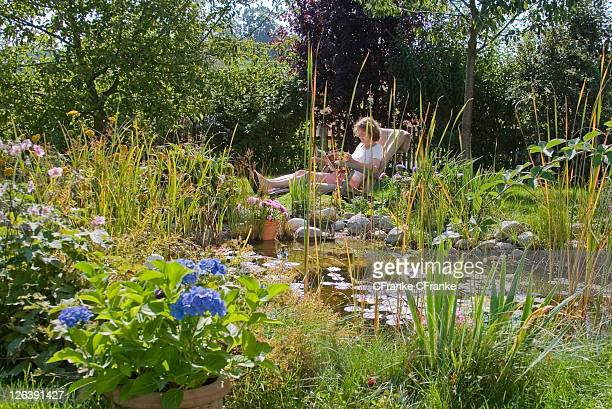 Side profile of woman reading magazine on lounge chair in lawn