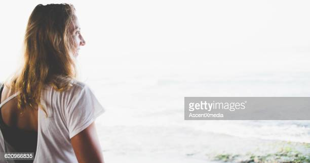 Side profile of young woman against waves