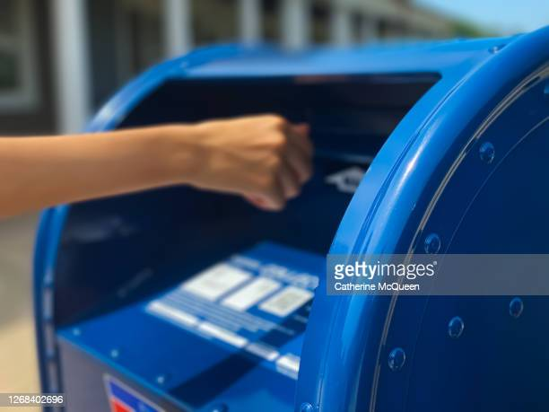 side profile view of mixed-race female mailing letter at traditional blue postal mailbox - voting by mail stock pictures, royalty-free photos & images