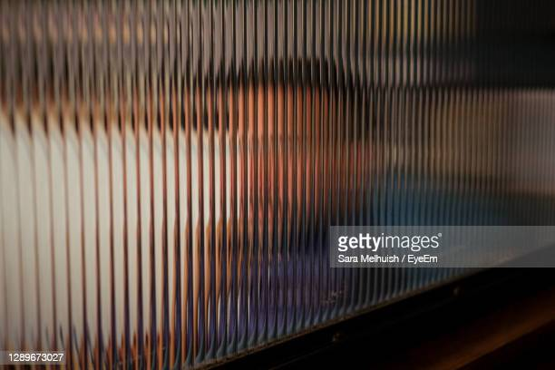 side shot of distorted face seen through textured glass - street style stock pictures, royalty-free photos & images