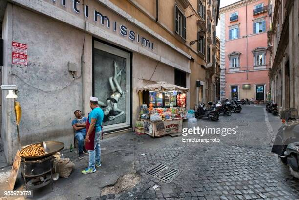 side street in rome with chestnut and small portable vendors chatting. - emreturanphoto stock pictures, royalty-free photos & images