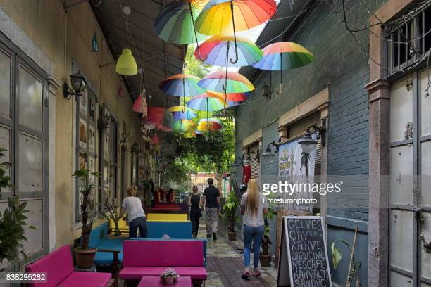 a side street with a coffee shop and people passing by in old shopping district kemeralti in izmir. - emreturanphoto stock pictures, royalty-free photos & images