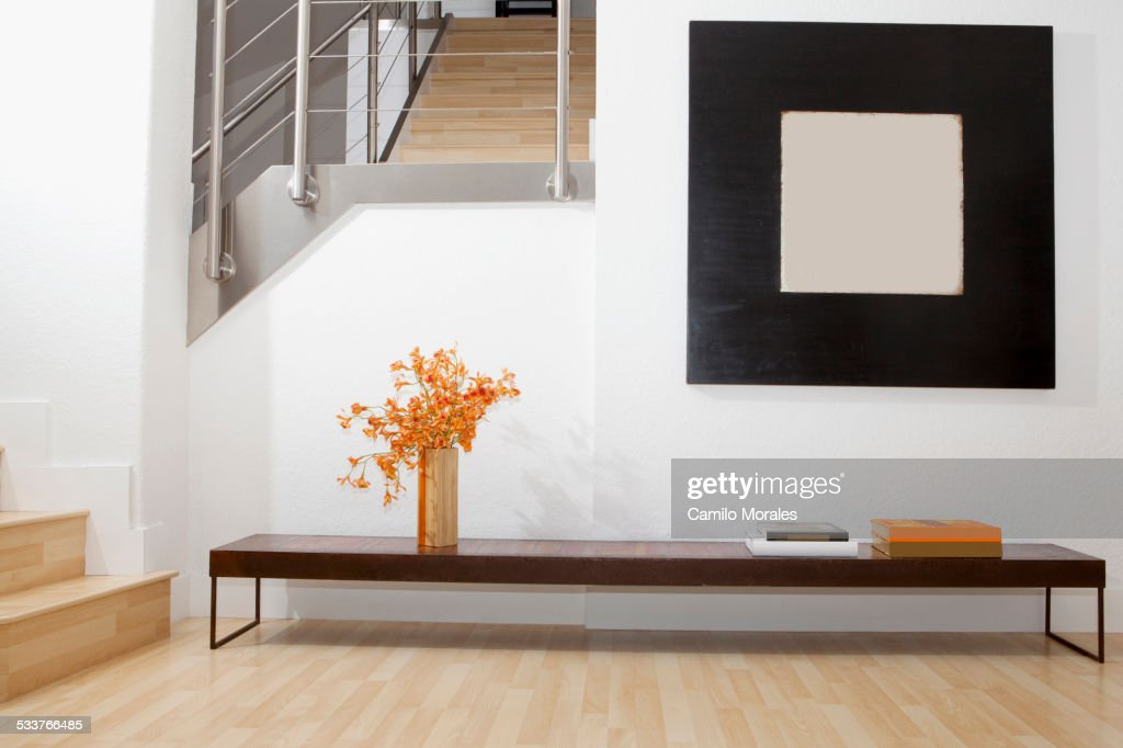 Side table, wall art and stairs in modern front room : Foto stock