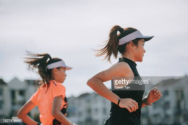 side view 2 asian chinese female athlete running at woman's track at track and field stadium in the morning - forward athlete stock pictures, royalty-free photos & images