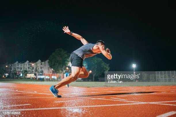 side view aerodynamic asian chinese male athletes sprint running at track and run towards finishing line at track and field stadium track rainy night - try scoring stock pictures, royalty-free photos & images