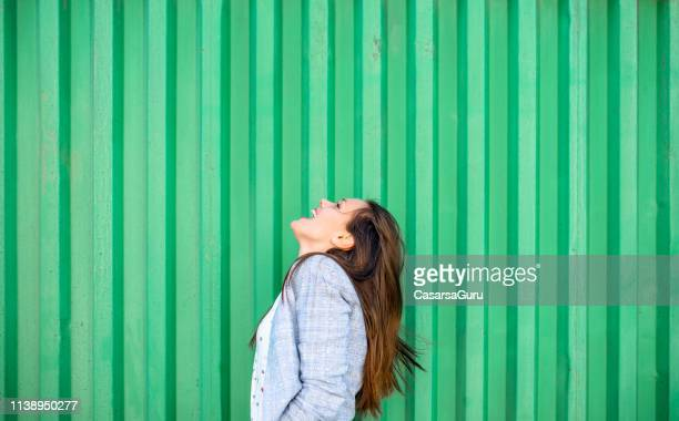 side view beautiful young happy adult woman laughing over green background - green background stock pictures, royalty-free photos & images