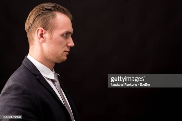 Side View Businessman Wearing Suit Against Black Background
