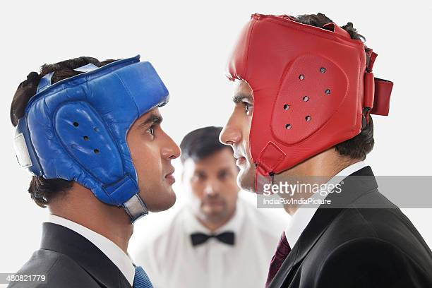 Side view close-up of angry businessmen wearing boxing helmets over white background
