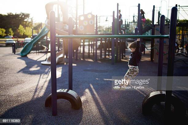 Side View Full Length Of Boy Hanging From Monkey Bars At Playground