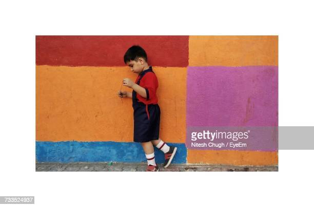 Side View Full Length Of Boy Standing By Colorful Wall