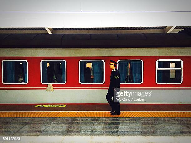 Side View Full Length Of Conductor Walking By Train At Railroad Station