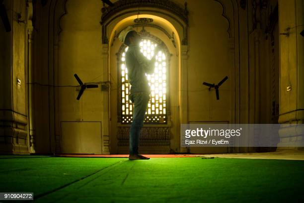 side view full length of man praying in mosque - namaz stock pictures, royalty-free photos & images