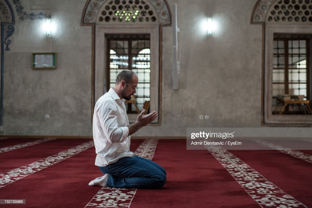 Side View Full Length Of Man Praying While Kneeling On Carpet In Mosque : Stock Photo