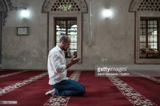 side view full length of man praying while kneeling on carpet in mosque - muslim praying stock pictures, royalty-free photos & images