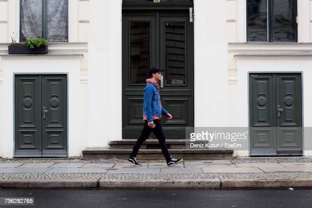 Side View Full Length Of Man Walking By Closed Door On Sidewalk