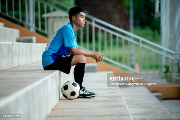 side view full length of soccer player sitting on steps - sports jersey stock pictures, royalty-free photos & images