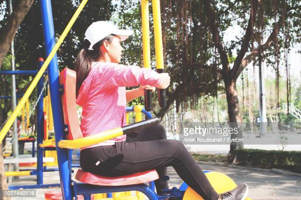 Side View Full Length Of Woman Sitting On Play Equipment At Park