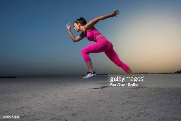 side view full length of young woman running against sky at sandy beach during sunrise - aikāne stock pictures, royalty-free photos & images