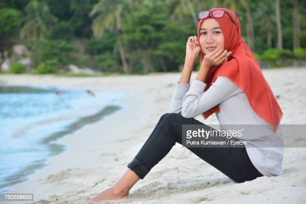 side view full length portrait of woman wearing red hijab at beach - muslim woman beach stock photos and pictures
