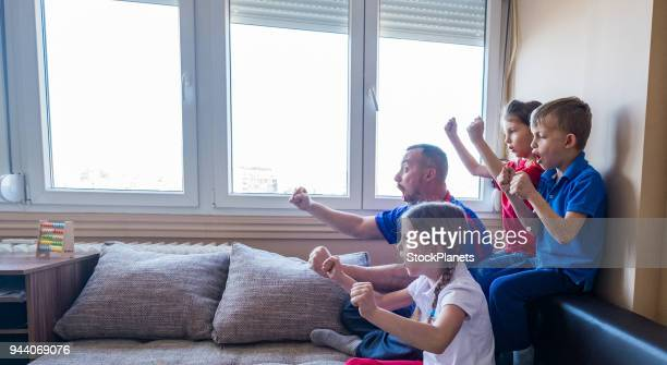 Side view happy family sitting and cheering for their football team