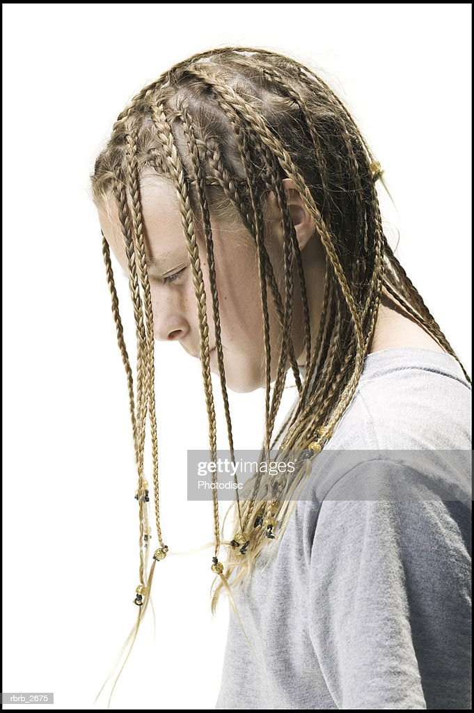 side view lifestyle portrait of a female child with blonde braids as she looks downward : Foto de stock
