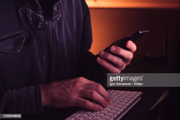side view midsection of computer hacker using smartphone device, novi sad, serbia - scammer stock pictures, royalty-free photos & images