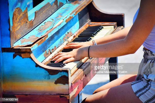 Side View Midsection Of Woman Playing Old Piano While Sitting Outdoors