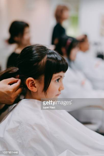 Side view of 4 year old little girl at hairdresser