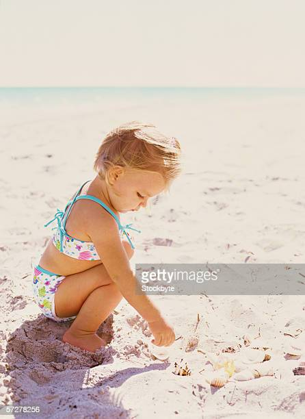 Side view of a baby girl playing on the beach