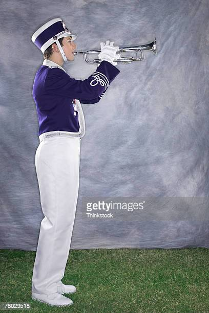 side view of a band member playing the trumpet. - marching band stock pictures, royalty-free photos & images