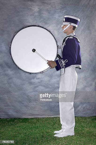 Side view of a band member with a bass drum ready to play.