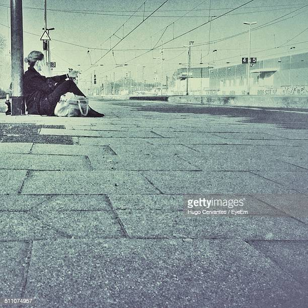 Side view of a beggar sitting on road