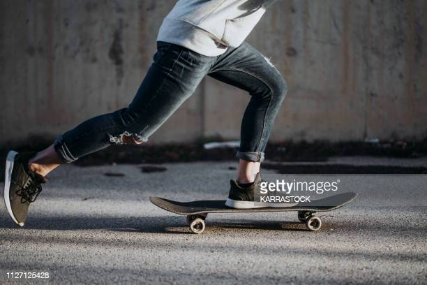 side view of a boy with a skateboard on the street at dawn. - longboard skating stock-fotos und bilder